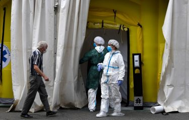 Healthcare workers wearing protective gear wait outside a field hospital set up for coronavirus cases outside the CAP Prat de la Riba primary care centre in Lerida (Lleida) on July 13, 2020. - A local court suspended a home confinement order imposed on more than 200,000 people in the Spanish region of Catalonia after an upsurge in virus cases. Catalonia officials ordered the home confinement on the city of Lerida and its surrounding areas a week after the zone had been placed under less strict lockdown. (Photo by Pau BARRENA / AFP) (Photo by PAU BARRENA/AFP via Getty Images)
