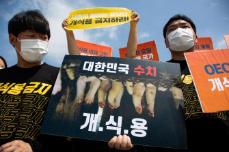 epa08548870 Members of an animal activist group hold placards during a campaign against eating dog meat, near the presidential house in Seoul, South Korea, 16 July 2020. The protesters voiced their objection to eating dog meat and call for the government to enact a law prohibiting dog-meat consumption.  EPA/JEON HEON-KYUN