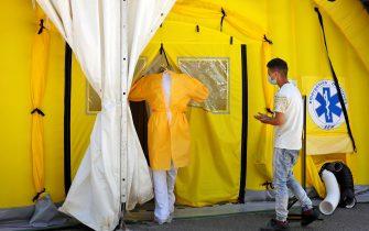 epa08549942 A health worker (L) and a patient enter into a field hospital that was recently built in Lleida, Catalonia, Spain, 16 July 2020. Regional authorities announced special movement restriction measures in the area of Segria in Lleida due to a coronavirus outbreak.  EPA/Susanna Saez