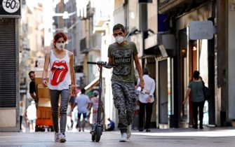 epa08549898 A couple wearing protective face masks take a stroll along downtown in Lleida, Catalonia, Spain, 16 July 2020. Regional authorities announced special movement restriction measures in the area of Segria in Lleida due to a coronavirus outbreak.  EPA/Susanna Saez