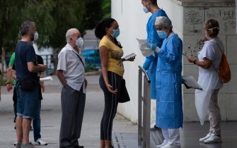 epa08549513 Residents stand in a queue to have a treatment outside the health primary center in the district of La Florida, in the city of L'Hospitalet, Barcelona, northeastern Spain, 16 July 2020. Catalan authorities carried out several special measures to avoid the spreading of the virus after a COVID-19 outbreak were registered in three suburbs of L'Hospitalet, the second most populated city of Catalonia.  EPA/ENRIC FONTCUBERTA