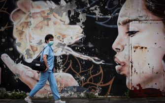 epa08549504 A paramedic walks past a graffiti while on her way to test residents for coronavirus disease (COVID-19) in the town of Tolosa, Basque Country, 16 July 2020. Residents are being tested for COVID-19 in the town after at least 22 positive cases were recorded so far.  EPA/JAVIER ETXEZARRETA