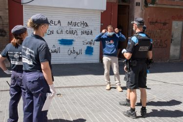 epa08549943 Police officers ask a man to wear a protective face mask in Lleida, Catalonia, Spain, 16 July 2020. Regional authorities announced special movement restriction measures in the area of Segria in Lleida due to a coronavirus outbreak.  EPA/Ramon Gabriel