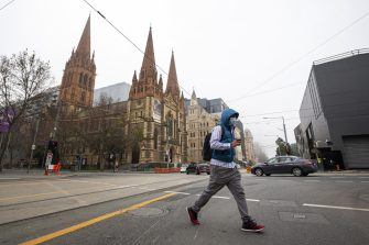epa08550978 A man wearing a mask crosses Flinders Street in Melbourne, Australia, 17 July 2020. Australia has recently seen a spike in coronavirus cases, with a cluster in the state of Victoria.  EPA/DANIEL POCKETT AUSTRALIA AND NEW ZEALAND OUT