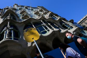 Visitors queue outside Spanish architect Antonio Gaudi's Casa Batllo on July 1, 2020 in Barcelona, on the first day it reopens to the public after more than three months of closure amid the new coronavirus pandemic. (Photo by LLUIS GENE / AFP) (Photo by LLUIS GENE/AFP via Getty Images)