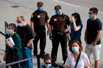 Security guards wearing face masks control visitors entering the Sagrada Familia basilica in Barcelona on July 4, 2020 as it reopens with a tribute to healthcare workers following a national lockdown to stop the spread of the novel coronavirus. (Photo by Josep LAGO / AFP) (Photo by JOSEP LAGO/AFP via Getty Images)
