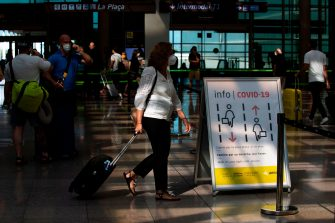 A passenger wearing a face mask walks with her luggage at the Josep Tarradellas Barcelona-El Prat airport in El Prat de Llobregat on July 6, 2020. - Spaniards endured one of the world's toughest lockdowns for three months from March as the country suffered one of Europe's worst coronavirus death tolls -- at least 28,385 -- and more than 250,000 cases. (Photo by Josep LAGO / AFP) (Photo by JOSEP LAGO/AFP via Getty Images)