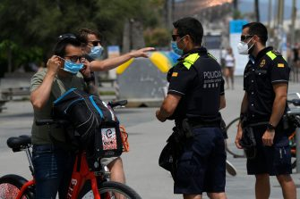 Catalan municipal police officers ask citizens to wear face masks at Barceloneta Beach in Barcelona on July 9, 2020. - Regional officials in Catalonia said they want to toughen the existing rules to make wearing masks compulsory in public, to stem a rising number of coronavirus cases. (Photo by LLUIS GENE / AFP) (Photo by LLUIS GENE/AFP via Getty Images)