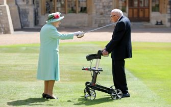 WINDSOR, ENGLAND - JULY 17: (EDITORS NOTE: Retransmission with alternate crop.) Queen Elizabeth II awards Captain Sir Thomas Moore with the insignia of Knight Bachelor at Windsor Castle on July 17, 2020 in Windsor, England. British World War II veteran Captain Tom Moore raised over £32 million for the NHS during the coronavirus pandemic.  (Photo by Chris Jackson/Getty Images)