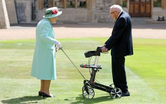 Britain's Queen Elizabeth II uses the sword that belonged to her father, George VI as she confers the Honour of Knighthood on 100-year-old WWII veteran Captain Tom Moore at Windsor Castle in Windsor, west of London on July 17, 2020. - British World War II veteran Captain Tom Moore was made a a Knight Bachelor (Knighthood) for raising over £32 million for the NHS during the coronavirus pandemic. (Photo by Chris Jackson / POOL / AFP) (Photo by CHRIS JACKSON/POOL/AFP via Getty Images)