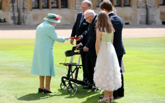Britain's Queen Elizabeth II (L) presents the insignia to 100-year-old veteran Captain Tom Moore during an investiture to confer the honour of knighthood upon him at Windsor Castle in Windsor, west of London on July 17, 2020. - British World War II veteran Captain Tom Moore was made a a Knight Bachelor (Knighthood) for raising over £32 million for the NHS during the coronavirus pandemic. (Photo by Chris Jackson / POOL / AFP) (Photo by CHRIS JACKSON/POOL/AFP via Getty Images)
