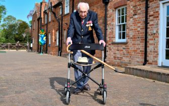 "TOPSHOT - British World War II veteran Captain Tom Moore, 99, poses with his walking frame doing a lap of his garden in the village of Marston Moretaine, 50 miles north of London, on April 16, 2020. - A 99-year-old British World War II veteran Captain Tom Moore on April 16 completed 100 laps of his garden in a fundraising challenge for healthcare staff that has ""captured the heart of the nation"", raising more than £13 million ($16.2 million, 14.9 million euros). ""Incredible and now words fail me,"" Captain Moore said, after finishing the laps of his 25-metre (82-foot) garden with his walking frame. (Photo by Justin TALLIS / AFP) (Photo by JUSTIN TALLIS/AFP via Getty Images)"