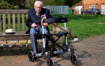 "British World War II veteran Captain Tom Moore, 99, sits on a bench in the village of Marston Moretaine, 50 miles north of London, on April 16, 2020. - A 99-year-old British World War II veteran Captain Tom Moore on April 16 completed 100 laps of his garden in a fundraising challenge for healthcare staff that has ""captured the heart of the nation"", raising more than £13 million ($16.2 million, 14.9 million euros). ""Incredible and now words fail me,"" Captain Moore said, after finishing the laps of his 25-metre (82-foot) garden with his walking frame. (Photo by JUSTIN TALLIS / AFP) (Photo by JUSTIN TALLIS/AFP via Getty Images)"