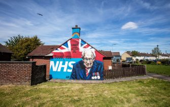 A street art graffiti mural, showing the logo of the NHS (National Health Service), and an image 100-year-old veteran Captain Tom Moore who raised over GBP 30 million for NHS charities, is pictured in east Belfast on May 5, 2020. - The number of people killed by the coronavirus in the UK stands at 32,313, according to official figures on May 5 2020, the second highest death toll in the world. Figures from the Office for National Statistics showed Britain had now overtaken Italy, which has reported 29,029 fatalities, and now only stands behind the US with 68,700 deaths, the largest single-country toll. (Photo by Paul Faith / AFP) (Photo by PAUL FAITH/AFP via Getty Images)