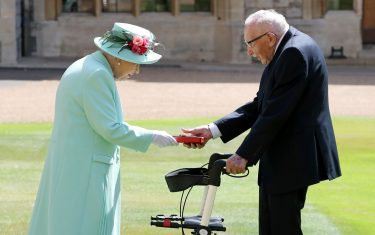 Britain's Queen Elizabeth II (L) presents the insignia to 100-year-old WWII veteran Captain Tom Moore during an investiture to confer the honour of knighthood upon him at Windsor Castle in Windsor, west of London on July 17, 2020. - British World War II veteran Captain Tom Moore was made a a Knight Bachelor (Knighthood) for raising over £32 million for the NHS during the coronavirus pandemic. (Photo by Chris Jackson / POOL / AFP) (Photo by CHRIS JACKSON/POOL/AFP via Getty Images)