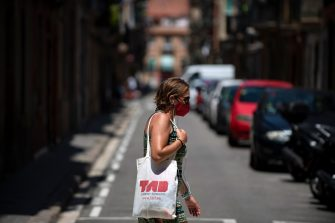 A woman wearing a face mask walks in the Barceloneta neighbourhood in Barcelona, on July 18, 2020. - Four million residents of Barcelona have been urged to stay at home as virus cases rise, while EU leaders were set to meet again in Brussels, seeking to rescue Europe's economy from the ravages of the pandemic. (Photo by Josep LAGO / AFP) (Photo by JOSEP LAGO/AFP via Getty Images)