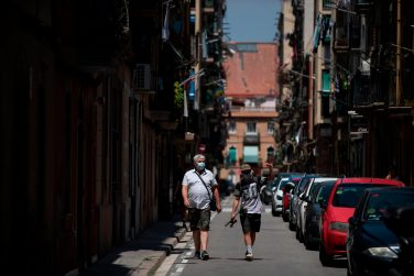Two people wearing face masks walk in the Barceloneta neighbourhood in Barcelona, on July 18, 2020. - Four million residents of Barcelona have been urged to stay at home as virus cases rise, while EU leaders were set to meet again in Brussels, seeking to rescue Europe's economy from the ravages of the pandemic. (Photo by Josep LAGO / AFP) (Photo by JOSEP LAGO/AFP via Getty Images)