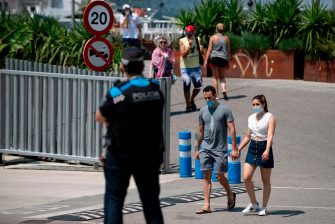 People stroll at Barcelona's harbour as a local police officer watches, on July 18, 2020. - Four million residents of Barcelona have been urged to stay at home as virus cases rise, while EU leaders were set to meet again in Brussels, seeking to rescue Europe's economy from the ravages of the pandemic. (Photo by Josep LAGO / AFP) (Photo by JOSEP LAGO/AFP via Getty Images)