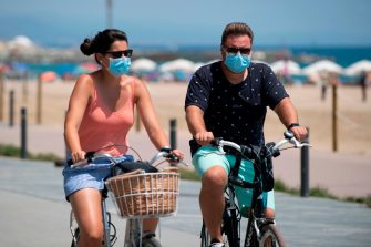 People wearing face masks ride a bicycle along a beach in Barcelona, on July 18, 2020. - Four million residents of Barcelona have been urged to stay at home as virus cases rise, while EU leaders were set to meet again in Brussels, seeking to rescue Europe's economy from the ravages of the pandemic. (Photo by Josep LAGO / AFP) (Photo by JOSEP LAGO/AFP via Getty Images)
