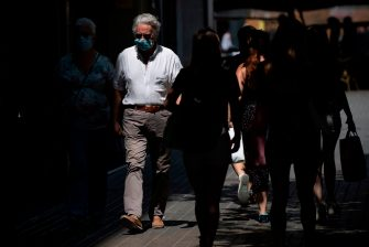 People wear face masks as they stroll in Barcelona on July 18, 2020. - Four million residents of Barcelona have been urged to stay at home as virus cases rise, while EU leaders were set to meet again in Brussels, seeking to rescue Europe's economy from the ravages of the pandemic. (Photo by Josep LAGO / AFP) (Photo by JOSEP LAGO/AFP via Getty Images)