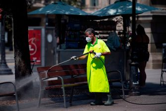 A municipal worker cleans a bench at Catalonia square in Barcelona on July 18, 2020. - Four million residents of Barcelona have been urged to stay at home as virus cases rise, while EU leaders were set to meet again in Brussels, seeking to rescue Europe's economy from the ravages of the pandemic. (Photo by Josep LAGO / AFP) (Photo by JOSEP LAGO/AFP via Getty Images)