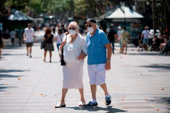 An elderly couple wearing face masks walks at Las Ramblas street in Barcelona on July 18, 2020. - Four million residents of Barcelona have been urged to stay at home as virus cases rise, while EU leaders were set to meet again in Brussels, seeking to rescue Europe's economy from the ravages of the pandemic. (Photo by Josep LAGO / AFP) (Photo by JOSEP LAGO/AFP via Getty Images)
