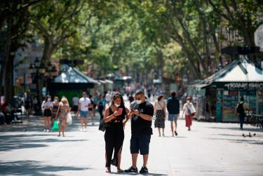 People wearing face masks look at their phones at Las Ramblas street in Barcelona on July 18, 2020. - Four million residents of Barcelona have been urged to stay at home as virus cases rise, while EU leaders were set to meet again in Brussels, seeking to rescue Europe's economy from the ravages of the pandemic. (Photo by Josep LAGO / AFP) (Photo by JOSEP LAGO/AFP via Getty Images)