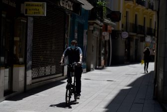 A man wearing a face mask rides a bike in Lerida (Lleida) on July 13, 2020. - A local court suspended a home confinement order imposed on more than 200,000 people in the Spanish region of Catalonia after an upsurge in virus cases. Catalonia officials ordered the home confinement on the city of Lerida and its surrounding areas a week after the zone had been placed under less strict lockdown. (Photo by Pau BARRENA / AFP) (Photo by PAU BARRENA/AFP via Getty Images)