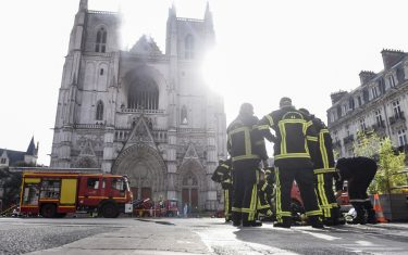 """Firefighters are at work to put out a fire at the Saint-Pierre-et-Saint-Paul cathedral in Nantes, western France, on July 18, 2020. - The major fire that broke out on July 18, 2020 inside the cathedral in the western French city of Nantes has now been contained, emergency services said. """"It is a major fire,"""" the emergency operations centre said, adding that crews were alerted just before 08:00 am (0600 GMT) and that 60 firefighters had been dispatched. (Photo by Sebastien SALOM-GOMIS / AFP) (Photo by SEBASTIEN SALOM-GOMIS/AFP via Getty Images)"""