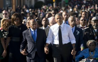 US President Barack Obama walks alongside Amelia Boynton Robinson (R), one of the original marchers, the Reverend Al Sharpton (2nd R), First Lady Michelle Obama (L), and US Representative John Lewis (2nd-L), Democrat of Georgia, and also one of the original marchers, across the Edmund Pettus Bridge to mark the 50th Anniversary of the Selma to Montgomery civil rights marches in Selma, Alabama, March 7, 2015. The event commemorates Bloody Sunday, when civil rights marchers attempting to walk to the Alabama capital of Montgomery to end voting discrimination against African Americans, clashed with police on the bridge. AFP PHOTO / SAUL LOEB        (Photo credit should read SAUL LOEB/AFP via Getty Images)