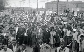 (Original Caption) Dr. Martin Luther King (center) leads an estimated 10,00 or more civil rights marchers out on the last leg of their Selma-to Montgomery march. Others identifiable in front row include: John Lewis, (2d from left) of SNCC; King's aide, Reverend Ralph Abernathy (3rd from left); Dr. Ralph Bunche (5th from left, looking to side); Mrs. King (next to King); and Rev. hosea Williams (carrying little girl, right).