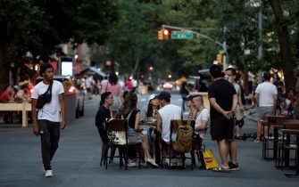 NEW YORK, NEW YORK - JULY 18: People without masks sit at a table on a closed-to-traffic St. Marks Place as the city moves into Phase 4 soon of re-opening following restrictions imposed to curb the coronavirus pandemic on July 18, 2020 in New York City. Governor Cuomo announced the city has been cleared for Phase 4 of re-opening starting on July 20. (Photo by Alexi Rosenfeld/Getty Images)