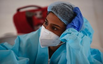 A health worker wearing a Personal Protective Equipment (PPE) suit waits for bus passengersto be tested for COVID-19 coronavirus at a makeshift test point at Sanathal, on the outskirts of Ahmedabad on July 17, 2020. - India on July 17 became the third country in the world to record one million coronavirus cases, following Brazil and the United States where infections also continued to surge. (Photo by SAM PANTHAKY / AFP) (Photo by SAM PANTHAKY/AFP via Getty Images)