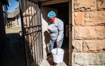 South African assistant cheesemaker Jeanet Mapula Mokwena (L) carries buckets of rennet, in Clarens, on July 13, 2020 in the small lab-turned-hut of Noah's Cheese, the small artisanal dairy run by Marietjie Crowther and her husband Danie. - Cheddar-making was put on hold when coronavirus hit an artisanal cheesery on the outskirts of Clarens, a town tucked in the foothills of South Africa's Maluti mountains. Hard cheeses requiring months of ripening were no longer viable, and the small business battled to stay afloat as sales plummeted. (Photo by MARCO LONGARI / AFP) (Photo by MARCO LONGARI/AFP via Getty Images)
