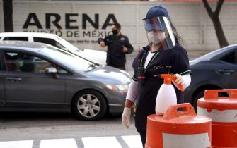 MEXICO CITY, MEXICO - JULY 17: A worker waits for the entrance of cars to sanitize them during a screening amid coronavirus pandemic at Arena Ciudad de MÈxico on July 17, 2020 in Mexico City, Mexico.  (Photo by Adrián Monroy/Medios y Media/Getty Images)