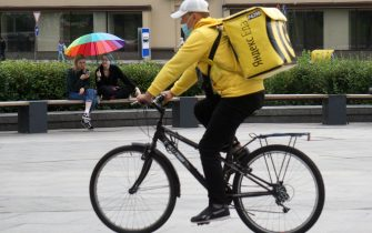 MOSCOW, RUSSIA - JULY,15 (RUSSIA OUT): A food delivery courier in protective mask rides a bicycle as two ladies sitting under umbrella in rainbow colors, on July,15,2020 in  Moscow, Russia. The requirement to wear masks and gloves to combat a spread of the Coronavirus (COVID-19) is still in effect in Moscow. (Photo by Mikhail Svetlov/Getty Images)