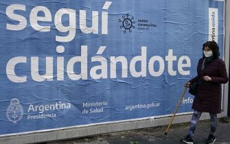 A woman passes by a government advertising requesting citizens to keep taking care during the novel coronavirus, COVID-19, pandemic, in Buenos Aires, on July 17, 2020. - The pandemic has killed at least 590,132 people worldwide since it surfaced in China late last year and more than 13.8 million have been infected, according to an AFP tally at 1100 GMT on Friday based on official sources. (Photo by Juan MABROMATA / AFP) (Photo by JUAN MABROMATA/AFP via Getty Images)