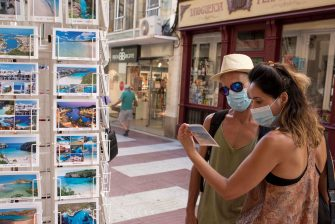 epa08556062 Two tourists look at a postcard at a souvenir shop in the island of Menorca, Balearic Islands, eastern Spain, 20 July 2020. The use of face mask in urban areas will be imposed in Balearic Islands from 21 July to avoid the spreading of COVID-19 disease.  EPA/DAVID ARQUIMBAU SINTES