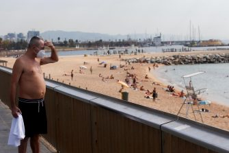 epa08556679 A man wearing a protective face mask looks on at the Barceloneta beach in Barcelona, northeastern Spain, 20 July 2020. At least four million Barcelona's residents and surrounding towns were imposed with a new set of restrictive measures to contain the COVID-19 infection from 18 July, after the number of positive cases remains on the rise and more patients are being hospitalized. Catalan regional authorities are sending text messages to residents at risk in order to prevent them from carrying out any social activity.  EPA/MARTA PEREZ