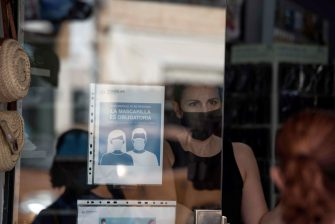 epa08556061 A woman wearing a face mask is seen inside a shop in the island of Menorca, Balearic Islands, eastern Spain, 20 July 2020. The use of face mask in urban areas will be imposed in Balearic Islands from 21 July to avoid the spreading of COVID-19 disease.  EPA/DAVID ARQUIMBAU SINTES