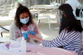 epa08556698 A health worker (L) takes a blood sample to perform a COVID-19 antibody test in Paris, France, 20 July 2020. Paris Mayor house organises free Covid test at Paris Plage (Paris beaches) area in an attempt to stop the widespread of the SARS-CoV-2 coronavirus causing the Covid-19 disease.  EPA/YOAN VALAT