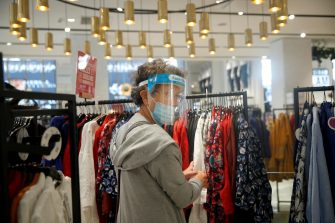 epa08556100 A woman wearing a face mask makes shopping on the Champs Elysee in Paris, France, 20 July 2020. From today, wearing a face mask inside closed public area becomes a duty in an attempt to stop the widespread of the SARS-CoV-2 coronavirus causing the Covid-19 disease.  EPA/YOAN VALAT