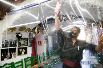 """GRANADA, SPAIN - JULY 18: Diego, worker of the flamenco tablao """"La Cueva de la Rocío"""" cleans the plastic that separates the public from the show, a security measure due to the threat of the Coronavirus on July 18, 2020 in Granada, Spain. The tablao flamenco 'La Cueva de la Rocio' reopened its doors on July 1st, 2020, after more than 3 months closed due to the Coronavirus pandemic. Security measures only allow 65 percent of capacity, and they are mostly national tourists.  (Photo by Carlos Gil/Getty Images)"""