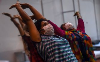 Patients perform yoga inside a ward at the Commonwealth Games (CWG) Village sports complex, temporarily converted into a COVID-19 coronavirus care centre, in New Delhi on July 16, 2020. (Photo by Money SHARMA / AFP) (Photo by MONEY SHARMA/AFP via Getty Images)