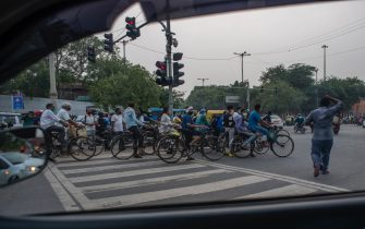 NEW DELHI, INDIA - JULY 17: Indian cyclists wait to cross a signal on a road on July 17, 2020  in New Delhi, India. With the highest single-day surge of 34,956 cases, Indias confirmed Covid-19 infections crossed the 1 million mark as the worlds third worst hit country grapples to deal with the impact of the global epidemic. Even as death toll due to the deadly virus mounted to 25,602 with record 687 fatalities in a day, according to data released by the health ministry on early Friday, Indian Prime Minister Narendara Modi in a televised address said the country was ensuring one of the best recovery rates in the world in its fight against Covid-19. (Photo by Yawar Nazir/Getty Images)