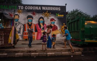NEW DELHI, INDIA - JULY 17: Indians stand in front of a mural on July 17, 2020  in New Delhi, India. With the highest single-day surge of 34,956 cases, Indias confirmed Covid-19 infections crossed the 1 million mark as the worlds third worst hit country grapples to deal with the impact of the global epidemic. Even as death toll due to the deadly virus mounted to 25,602 with record 687 fatalities in a day, according to data released by the health ministry on early Friday, Indian Prime Minister Narendara Modi in a televised address said the country was ensuring one of the best recovery rates in the world in its fight against Covid-19. (Photo by Yawar Nazir/Getty Images)
