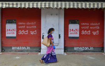 A woman walks past a closed shop in a street during a lockdown to contain the surge of COVID-19 coronavirus cases, in Bangalore on July 20, 2020. - India on July 17 hit a million coronavirus cases, the third-highest total in the world, with no sign yet of the infection curve flattening as new cases emerge in rural areas. More than 25,000 people have died nationally. (Photo by Manjunath Kiran / AFP) (Photo by MANJUNATH KIRAN/AFP via Getty Images)