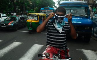 A police officer (unseen) gives a mask to a cyclist as part of an awareness campaign to control the spread of the of the COVID-19 coronavirus, in Kolkata on July 20, 2020. - Coronavirus cases in India passed one million on July 17, official data showed as authorities struggle to check the spread of the deadly pandemic across the world's second-most populous nation. (Photo by Dibyangshu SARKAR / AFP) (Photo by DIBYANGSHU SARKAR/AFP via Getty Images)