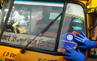A police officer paste a sticker on the wind-screen of an auto-rickshaw as part of an awareness campaign to control the spread of the of the COVID-19 coronavirus, in Kolkata on July 20, 2020. - Coronavirus cases in India passed one million on July 17, official data showed as authorities struggle to check the spread of the deadly pandemic across the world's second-most populous nation. (Photo by Dibyangshu SARKAR / AFP) (Photo by DIBYANGSHU SARKAR/AFP via Getty Images)
