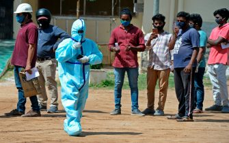 A health worker wearing Personal Protective Equipment (PPE) gear walks past the residents standing in queue to register their names at a free testing centre for the COVID-19 coronavirus, at MedchalMalkajgiri district on the outskirts of Hyderabad July 21, 2020. - India on July 17 hit a million coronavirus cases, the third-highest total in the world, with no sign yet of the infection curve flattening as new cases emerge in rural areas. More than 25,000 people have died nationally. (Photo by NOAH SEELAM / AFP) (Photo by NOAH SEELAM/AFP via Getty Images)